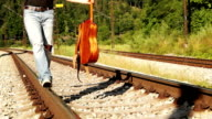 A teenage boy clad in torn-up jeans walks along the rail balancing with a guitar video