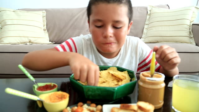 Teenage boy eating nachos video
