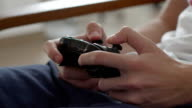 Teenage boy using game pad controller to play video games, in the end throwing the controller, close up video