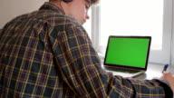 Teenage boy wearing headphones writing at desk in his bedroom, shot on R3D video