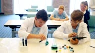 Teenage boys work on chemical experiment in science class video