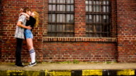 Teenage couple kissing in front of old industry building video
