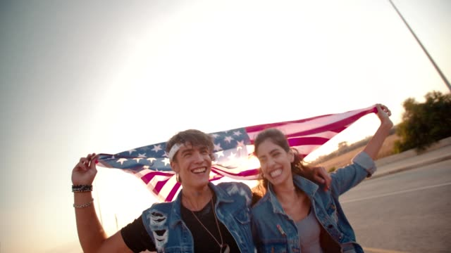 Teenage couple on a road trip running with American flag video