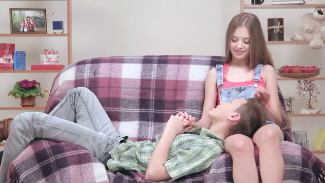 Teenage couple resting together in armchair, girl comfort, calm boy video