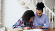 Teenage curly haired mixed race young girl sitting at the table concentrating focused learning lessons and her elder sister helps her studying video