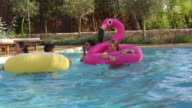 Teenage friends have fun with inflatables in a swimming pool, shot on R3D video
