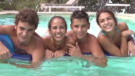 Teenage Friends Having Fun On Airbed In Swimming Pool video