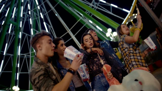 Teenage friends having fun on night out at amusement park video