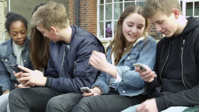Teenage Friends In Town Using Mobile Phones Shot On R3D video