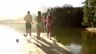 Teenage friends running and jumping into lake video
