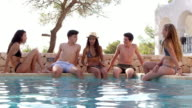 Teenage friends sitting at the edge of a swimming pool talking, shot on R3D video