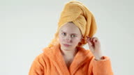 Teenage girl after shower cleaning her ear with cotton swab looking in mirror video