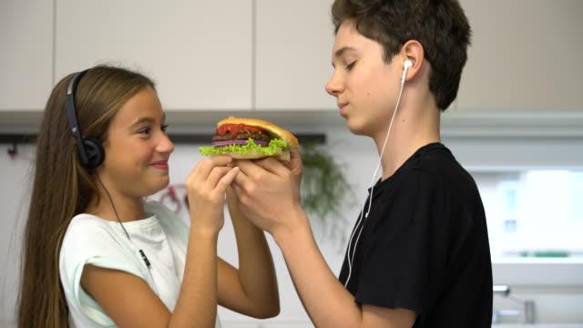 teenage girl and boy eating hamburgers together video