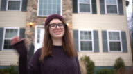Teenage girl before her house in the community video
