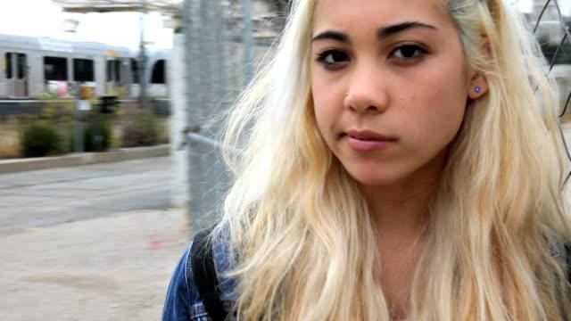 Teenage girl chews gum waits by train video
