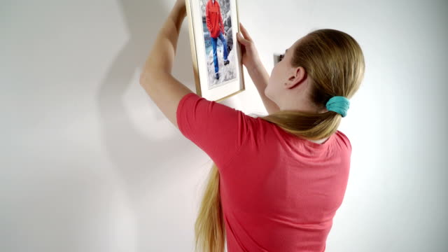 Teenage girl hanging family framed photos on wall at home video