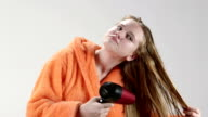 Teenage girl in bathrobe blow drying her wet long hair with hairdryer after shower video