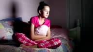 Teenage girl in pajamas sitting on bed watching TV video