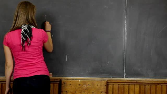 teenage girl in retro classroom writes on blackboard video