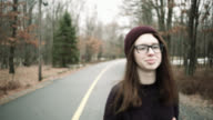 Teenage girl in the sweater and hat walking on the community road in winter video