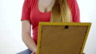 Teenage girl looking at the framed photo print in her hands video