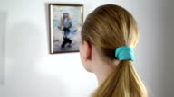 Teenage girl looking at the framed photographs of children hanging on the wall video