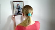 Teenage girl looks at a framed photograph of herself as a child video