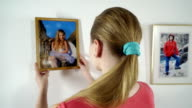 Teenage girl looks at framed photo of a little girl dressed in ballet dress video