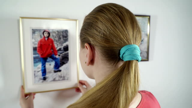Teenage girl looks at the family framed photo prints hanging on the wall video