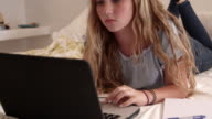 Teenage girl on bed using smartphone and laptop, close up, shot on R3D video