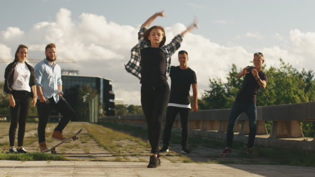 Teenage Girl Performing Modern Dance for Group of Friends Outdoors in Urban Environment. video