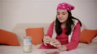 Teenage girl putting money into savings jar video