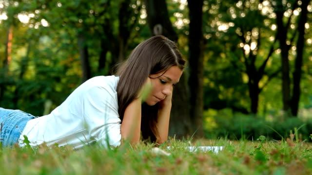 Teenage girl reading book on meadow video