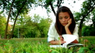 Teenage girl reading book on meadow video