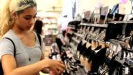 Teenage girl shopping for makeup. Shakes nail polish. video