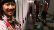 Teenage girl smiles in school hallway video
