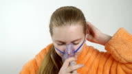Teenage girl using nebulizer with breathing mask at home inhaling the medication video
