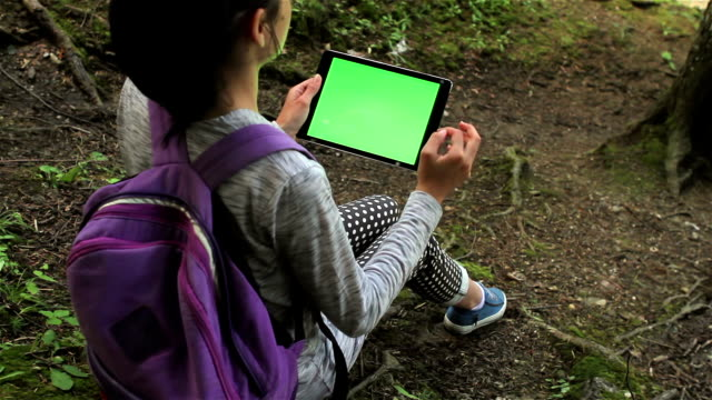 Teenage girl using tablet pc with green screen video
