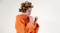 Teenage girl wearing bathrobe in hair curlers applying nail polish on fingernail video