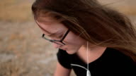 Teenage girl with eyeglasses sitting on the ground and listening to the music, close up video