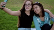 Teenage girl with her mother taking self ie in the park video