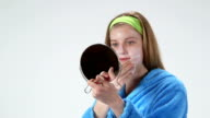 Teenage girl with problem skin wiping off homemade facial mask video