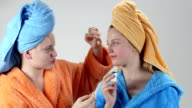 Teenage girls in bathrobes and towels on heads applying face clearing lotion video