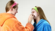 Teenage girls in bathrobes applying homemade facial cream mask for teenagers video