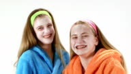 Teenage girls in bathrobes with a homemade facial cream mask laughing video