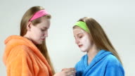 Teenage girls in bathrobes with applied homemade facial cream masks video