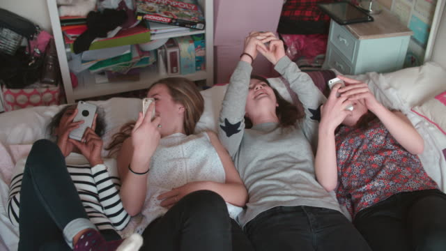 Teenage Girls Lying On Bed Using Mobile Phones At Home video