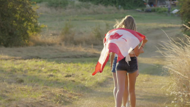 Teenage girls running with Canadian Flag celebrating Independence video