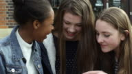 Teenage Girls Using Mobile Phones In Town Shot On R3D video