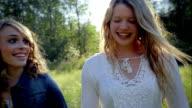 2 Teenage Girls Walks Through Meadow, Talking, In Slow Motion video